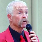 Patt Abbatt holding a microphone and wearing a red tie and jacket