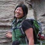 Emily Wei standing in front of an outcrop smiling