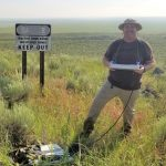Michael Levenson standing in front of and unexploded bomb field with a GPR intena