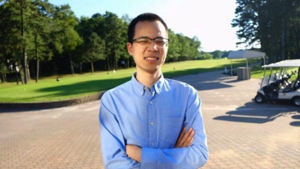 Zhifeng Hu wearing a blue button up shirt and glasses with his arms crossed standing in front of a wooded area