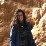 Xiomara Rosenblatt wearing a blue jacket and black leggings standing with hydrothermal rocks in the background