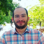 Guilherme de Melo wearing a plaid shirt with greenery in the background