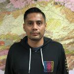 Hernan Guerrero standing in front of a map